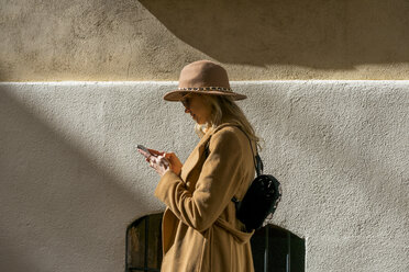 Fashionable young woman at a building using cell phone - AFVF00235