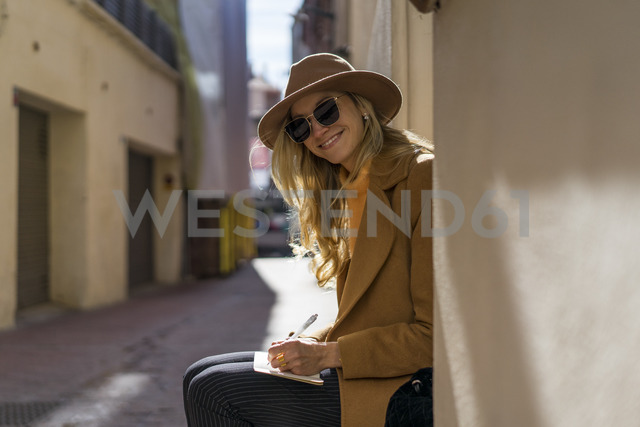 Fashionable young woman sitting at house entrance writing in notebook - AFVF00238