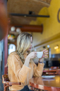 Pensive young woman in a cafe holding cup of coffee - AFVF00244