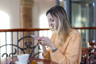Smiling young woman in a cafe using cell phone - AFVF00247