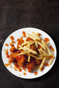Plate of Chicken Nuggets with sweet chili sauce and French Fries on dark metal - CSF28941