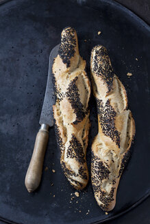 Two baguettes with black cumin and a bread knife on dark metal - CSF28962
