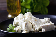 Feta, herbes and basil leaves on black plate, close-up - CSF28986