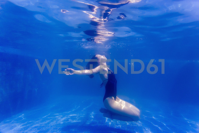 Young woman underwater in a swimming pool - KNTF00985