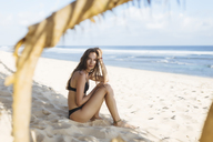 Indonesia, Bali, portrait of attractive young woman sitting on the beach - KNTF00991