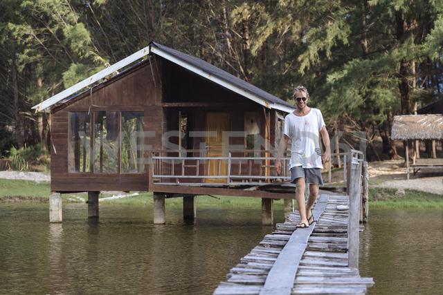 Indonesia, Sumatra, young man walking on footbridge - KNTF00997