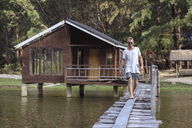 Indonesia, Sumatra, young man walking on footbridge - KNTF00997