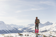 Switzerland, Engadin, hiker in mountainscape looking at view - MRAF00261