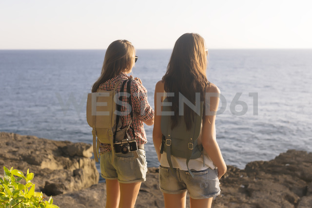 Indonesia, Bali, Lembongan island, two young women at ocean coastline - KNTF01001