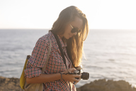 Indonesia, Bali, Lembongan island, young woman with camera at ocean coastline - KNTF01004