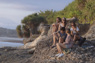 Indonesia, Bali, Lembongan island, friends having a drink at ocean coast - KNTF01007