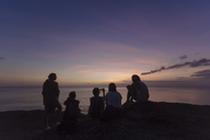 Indonesia, Bali, Lembongan island, friends at ocean coast at dusk - KNTF01010