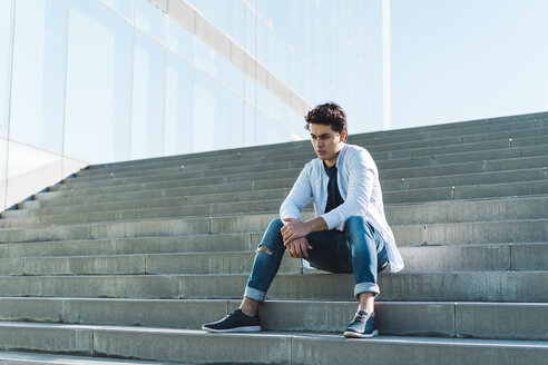 Serious young man sitting on stairs outdoors - AFVF00254