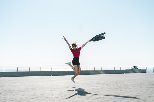 Fashionable young woman jumping on waterfront promenade - AFVF00269