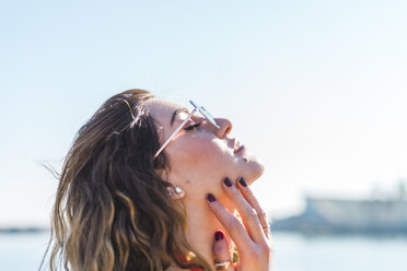 Portrait of young woman wearing sunglasses under blue sky - AFVF00275