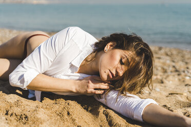 Attractive young woman lying in sand on the beach - AFVF00278