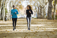 Two smiling young women running in park listening to music - JSRF00003