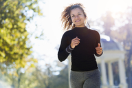 Smiling young woman with earphones running in park - JSRF00006