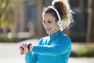 Sportive young woman with headphones checking the time - JSRF00009