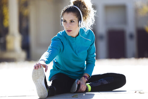 Young woman with headphones stretching - JSRF00012