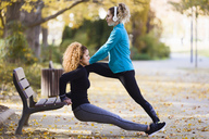 Two sportive young women stretching in park - JSRF00018