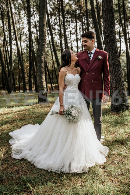 Happy bride and groom standing in forest - DAPF00889