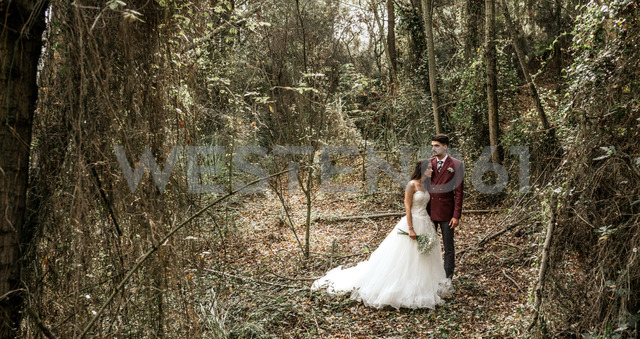Bride and groom standing in forest - DAPF00901