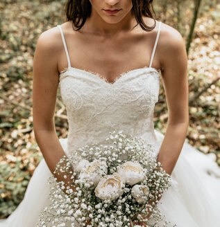 Close-up of bride holding bouquet of flowers in forest - DAPF00904