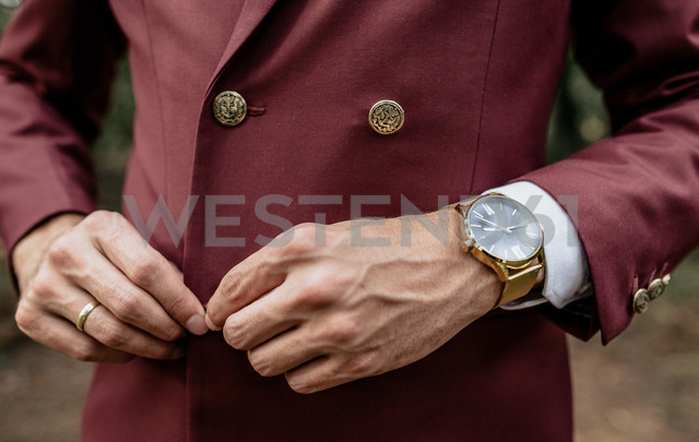 Close-up of man wearing a suit and golden watch buttoning his jacket - DAPF00907