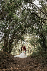 Bride and groom kissing passionately under big trees in the forest - DAPF00910