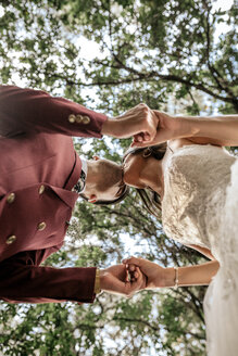 Bride and groom holding hands and kissing under a tree - DAPF00913