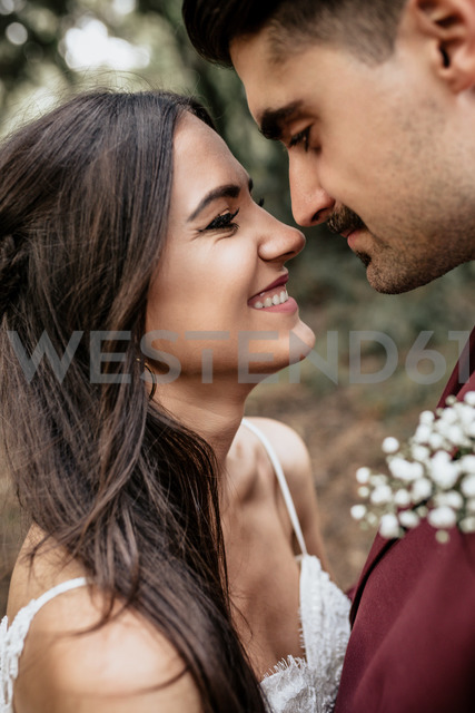 Portrait of happy and smiling bride looking at man with moustache outdoors - DAPF00916