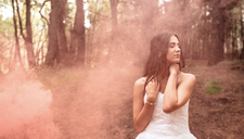 Woman with closed eyes wearing wedding dress in forest surrounded by clouds of smoke - DAPF00919