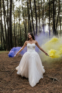 Woman wearing wedding dress in forest holding smoke torches - DAPF00922