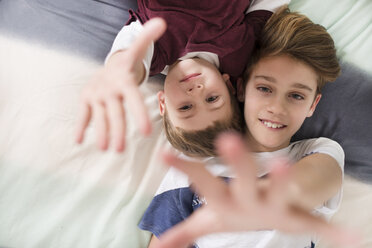Top view of two smiling brothers lying on bed reaching out their hands - SKCF00337