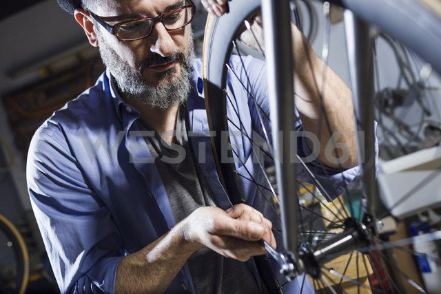 Man working on bicycle in workshop - JSRF00020