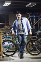 Portrait of confident man in bicycle workshop - JSRF00026