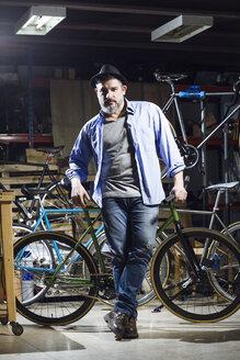 Portrait of confident man in bicycle workshop - JSRF00026