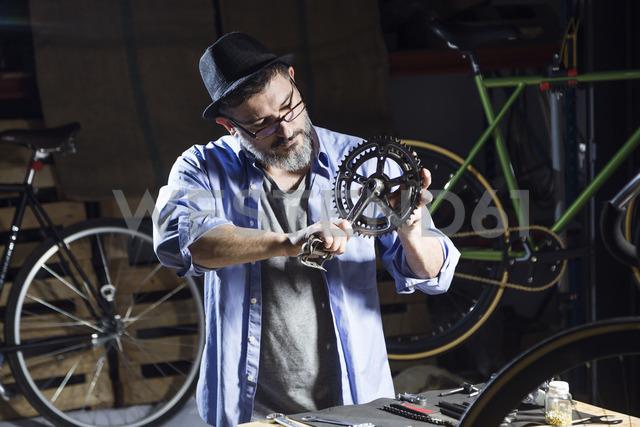 Man working on pedal in bicycle workshop - JSRF00029