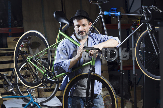 Portrait of confident man in workshop carrying bicycle - JSRF00038