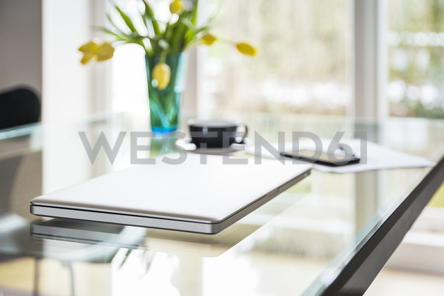 Laptop on glass table in living room - JHAF00014
