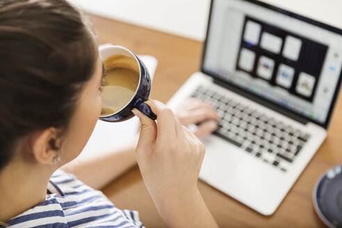 Young woman having a coffee break from working with laptop at home - JHAF00017