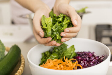 Hands putting fresh lettuce into a bowl with different vegetables - JHAF00023