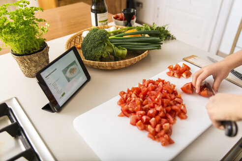 Young woman cutting tomatoes on kitchen counter and reading recipe on tablet - JHAF00026