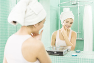 Young woman applying facial moisturizer at mirror in bathroom - JHAF00032