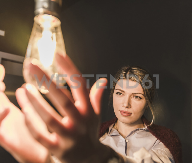Young woman reaching for illuminated light bulb - UUF12829