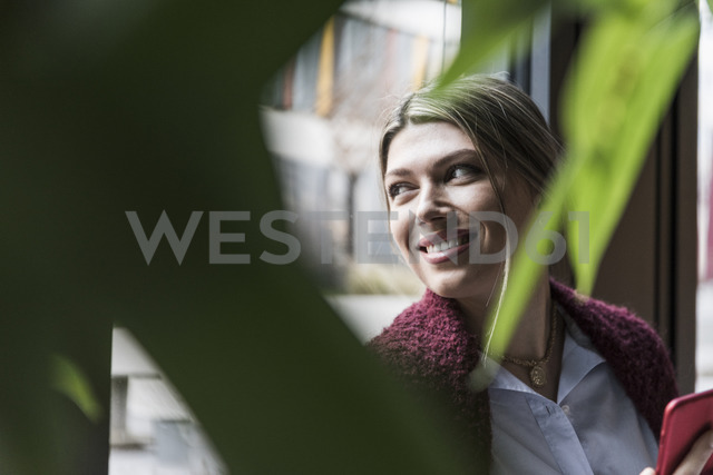Smiling young woman at the window - UUF12832