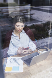 Young woman with cell phone, laptop and documents behind windowpane - UUF12835