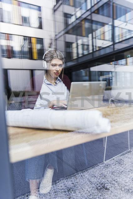 Young woman wearing headphones using laptop behind windowpane - UUF12838