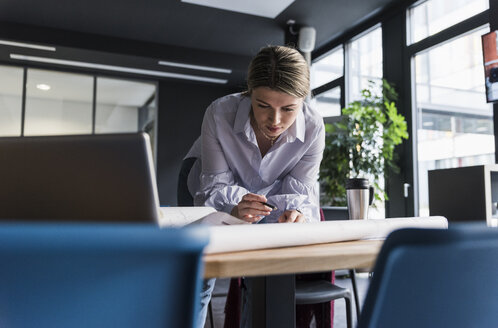 Young woman working on plan at table in office - UUF12841